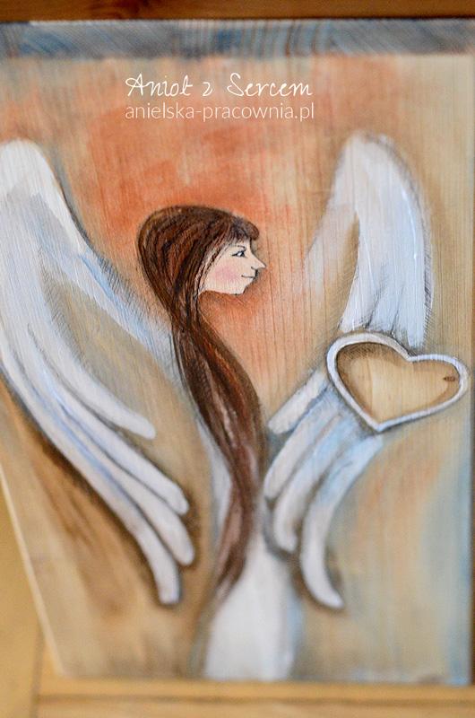 Anioł z Sercem to druga propozycja w nowej formule Aniołów na prostokątnych heblowanych deskach o dokładnie takich samych, powtarzalnych wymiarach